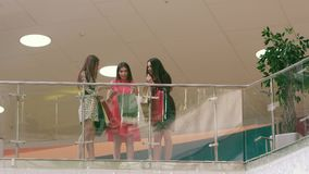 Three caucasian women in shopping center showing their new clothes to each other stock video footage