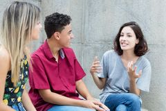 Three caucasian young adults in discussion stock photos