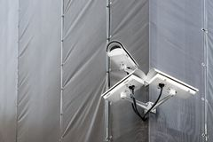 Three CCTV cameras on corner of building under restoration or renewal outdoors. Security cameras on wall of construction building stock photo