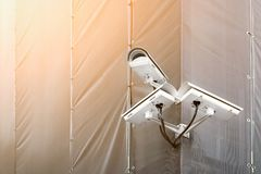 Three CCTV cameras on corner of building under restoration or renewal outdoors. Security cameras on wall of construction building royalty free stock photos