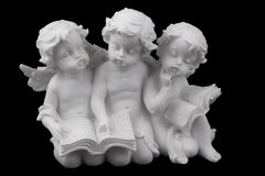 Three ceramic white angels read the book, dreaming and thinking. Isolated on black Stock Images