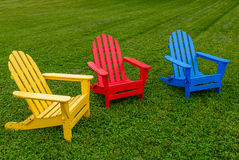 Three Chairs Yellow Red Blue on Grass. Three Adirondack chairs in colors lemon yellow, fire engine red and sky blue on a field of green grass and clover Stock Photos