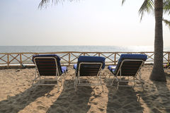 Three chairs by the beach shore. Stock Photography