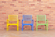 Three chairs on the brick wall Stock Photos