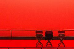 Three chairs on empty red stage royalty free stock photos