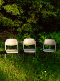 Three chairs in garden Stock Images