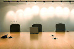 Three chairs and laptop in corporate meeting room. Three chairs lined up with a laptop in front in executive boardroom setting of modern day clean office. Space Stock Photo