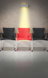 Three chairs in line and light on the middle chair Royalty Free Stock Images