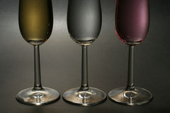 Three champagne. Golden, white and pink champagne, backlit against dark background Royalty Free Stock Photography