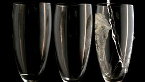 Three champagne flutes with one being filled stock video