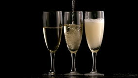 Three champagne flutes topped up stock video