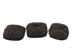 Three charcoal briquets. Three small charcoal briquets used for barbecue isolated on white Royalty Free Stock Images