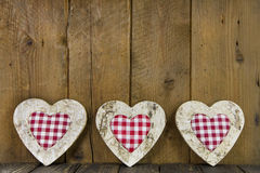 Three checked hearts of wood on a wooden background. Royalty Free Stock Images