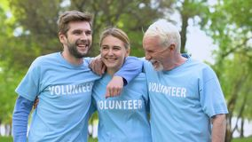 Three cheerful activists in volunteer t-shirts hugging, eco project achievement stock footage