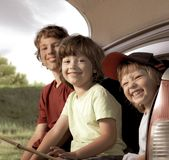 Three cheerful child sitting in the trunk of a car on nature stock image
