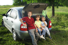 Three cheerful child sitting in the trunk of a car Royalty Free Stock Image