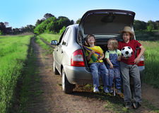 Three cheerful child sitting in the trunk of a car Stock Image