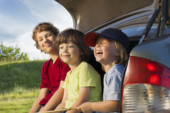 Three cheerful child sitting in the trunk of a car Stock Images