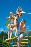 Three cheerful children on bar at the playground stock images