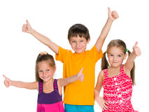Three cheerful children hold their thumbs up Stock Photos