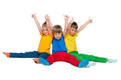 Three cheerful children hold their thumbs up. On the white background Royalty Free Stock Photography
