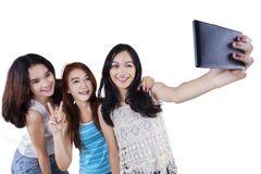 Three cheerful girls taking selfie Stock Image