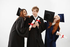 Three cheerful graduate classmates celebrating smiling rejoicing over white background. Future lawyers or medics Royalty Free Stock Photo