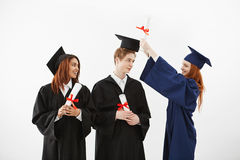 Three cheerful graduates smiling speaking fooling holding diplomas over white background. Three cheerful graduates in caps and mantles smiling speaking fooling Royalty Free Stock Images