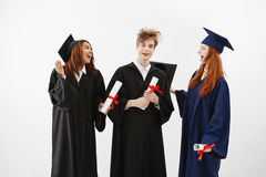 Three cheerful graduates smiling speaking fooling holding diplomas over white background. Three cheerful graduates in caps and mantles smiling speaking fooling Royalty Free Stock Image