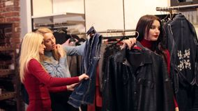 Three cheerful happy girlfriends are looking at clothes in a modern store. stock footage