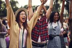 Three cheerful hipster friends enjoying outdoor concert stock images