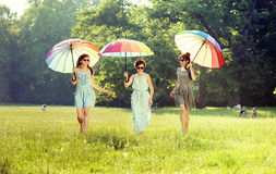 Three cheerful ladies walking on the summer meadow Stock Images