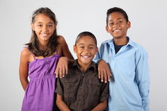 Three cheerful school friends share happy moment. Group of three happy young ethnic school children ages 9 and 10 share a moment of happy laughter during studio Stock Photo