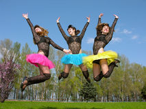 Three cheerful showgirls jumping outdoors stock photography