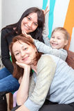 Three cheerful sisters embracing together Stock Photos