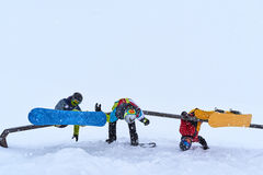 Three cheerful snowboarders hung on the rail for tricks Stock Images