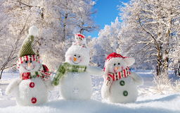 Three cheerful snowman in the snow. Royalty Free Stock Photos