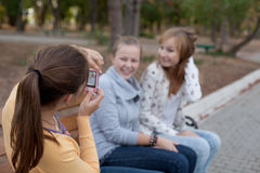 Three cheerful student girls making photos Royalty Free Stock Photos