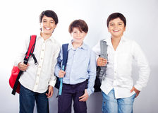 Three cheerful teenagers. On white background, back to school, best friends classmates, preteens standing and smiling  with backpacks and textbooks, knowledge Stock Photography