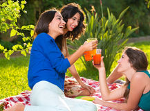 Three cheerful women drinks on a sunny afternoon Royalty Free Stock Photography
