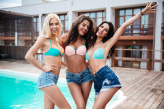 Three cheerful women standing together near swimming pool in summer Stock Photo