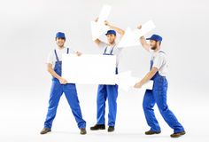 Three cheerful workers with empty banner Stock Photos