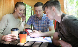 Three cheerful young people meeting and using smartphone with laptop at outdoor cafe. Stock Photos