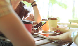 Three cheerful young people meeting and using smartphone with laptop at outdoor cafe. Stock Images
