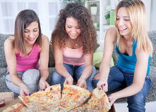 Three cheerful young woman eating pizza at home Stock Photography