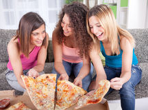 Three cheerful young woman eating pizza at home Stock Image