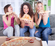 Three cheerful young woman eating pizza at home Stock Photos