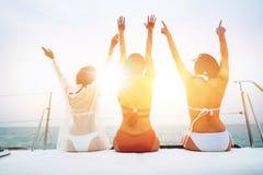 Free Three Cheerful Young Women In Bikini Sitting On Boat And Admiring Sea View Royalty Free Stock Photos - 149546328