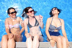 Three cheerful young women simulate that they sit over a pools edge with a water wall backwards Stock Photography