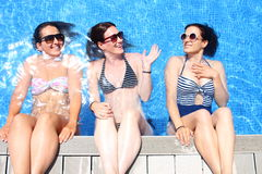Three cheerful young women simulate that they sit over a pools edge with a water wall backwards Royalty Free Stock Photography